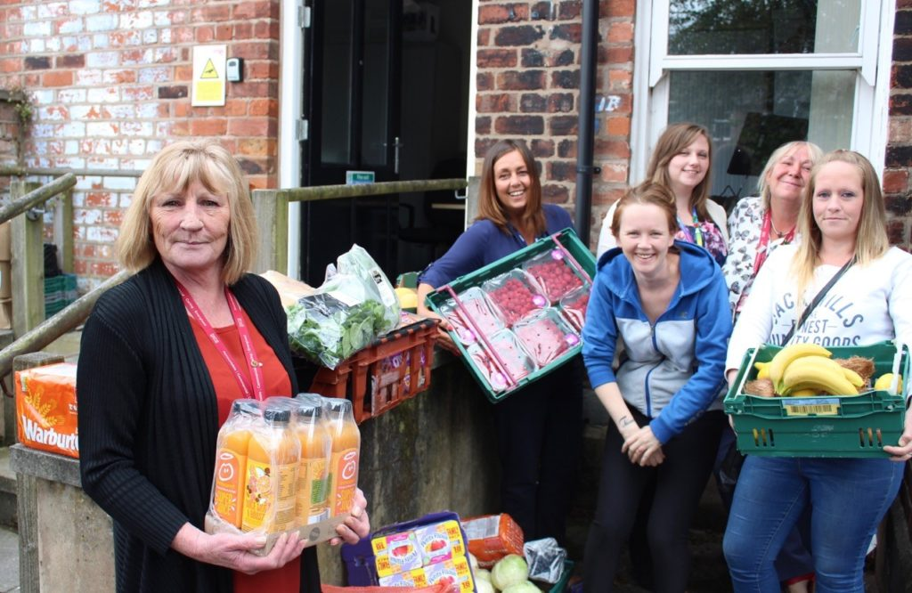 Staff at Astley Lodge holding surplus food delivered to them by FareShare